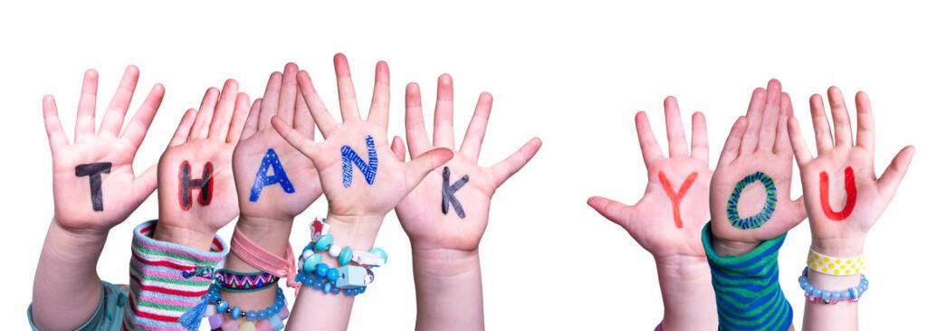 Nach oben gestreckte Kinderhände. Auf den Händen steht ``Thank You``